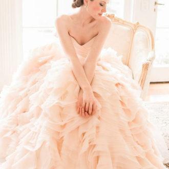 novia sentada con vestido de novia pomposo en color rosa pastel