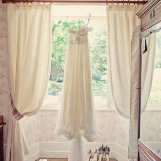 vestido de novia colgado en percha en ventana