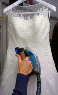 vestido de novia colgado en percha siendo planchado