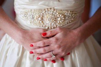 novia con manos vientre con la manicura en color rojo