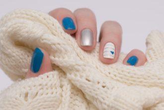 mano con manicura azul cogiendo lana blanca