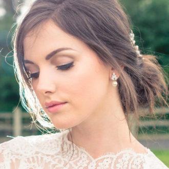 novia con el pelo recogido y pendientes de perlas