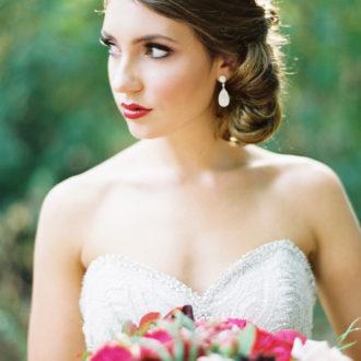 novia con vestido escote corazón luciendo pendientes de diamantes y ramo