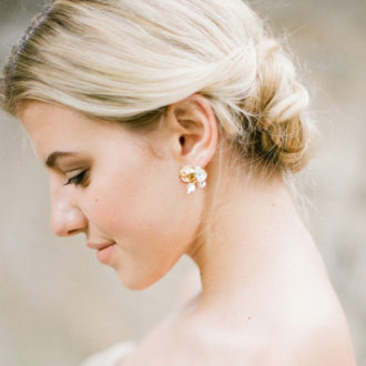 novia de perfil con pendientes de oro y cristales con motivos florales
