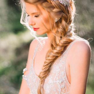novia rubia con trenza lateral y broche plateado