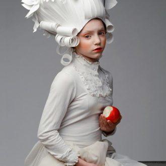 mujer con peluca barroca de papel de Asya Kozina y manzana mordida en la mano