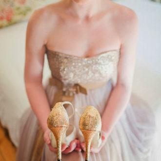 novia con vestido de novia glitter palabra de honor sosteniendo zapatos glitter