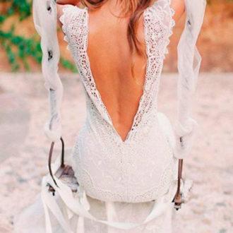 novia con escote en la espalda y tocado en un columpio
