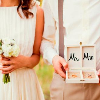pareja de novios millennial enseñando sus alianzas de manera original