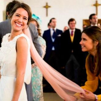 novia sonriendo con velo en color rosa