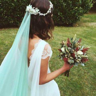 novia con velo en color verde y ramo de flores