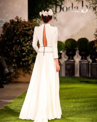 novia con vestido con detalles en color negro de espalda en pasarela