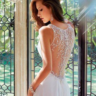 novia con vestido de escote cerrado posando con sus joyas de boda