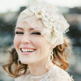 novia con tocado sonriendo a la cámara