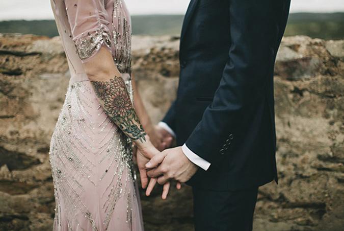 pareja de novios cogidos de las manos, novia con tatuaje en el brazo derecho