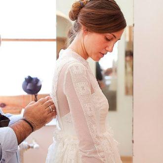 diseñador arreglando la parte de atrás de un vestido de novia a medida