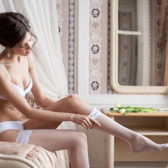 novia en lencería poniéndose las medias