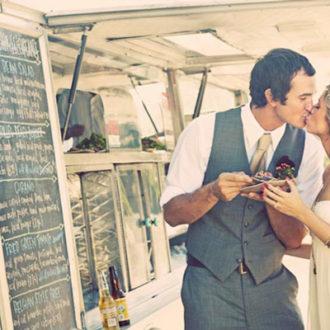 pareja slow wedding con comida en la mano besándose